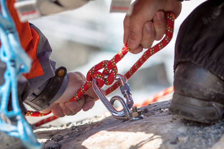 Cropped Image Of Person Tightening Rope While Climbing Rock