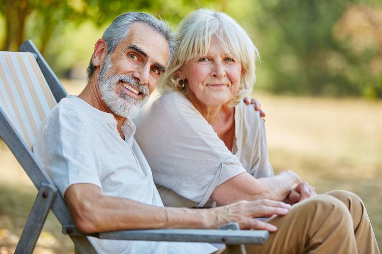 Portrait Of Senior Couple Sitting At Park