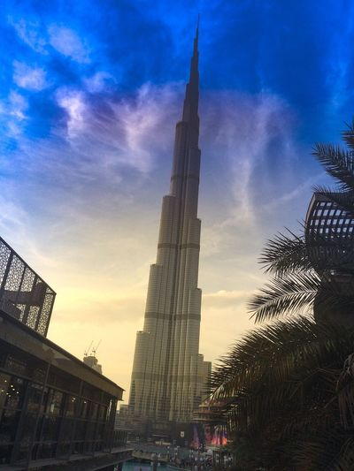 Dubai, Burj Khalifa Architecture Building Exterior Built Structure Sunset Sky Famous Place Travel Destinations Incidental People Silhouette Low Angle View Tourism City Tower History City Life Place Of Worship Church Cloud - Sky Blue Tall - High First Eyeem Photo