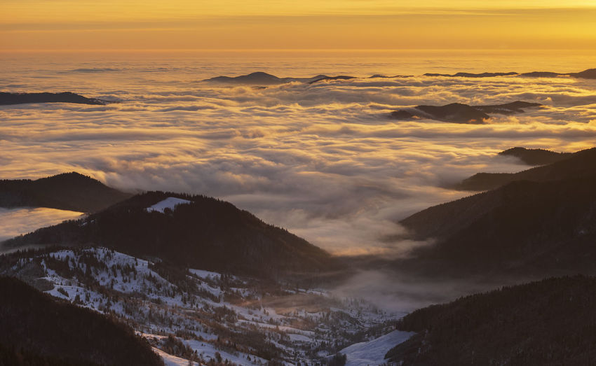 The beauty of winter on the snowy mountains at sunrise with alpine sea. ceahlau mountains, romania