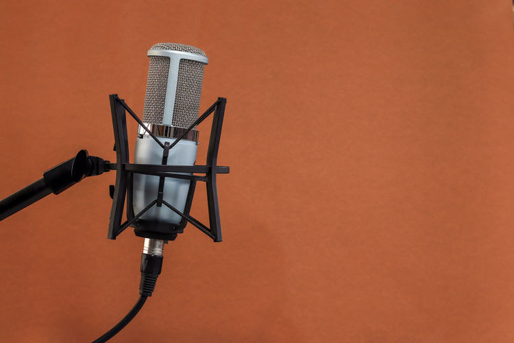 Microphone on Brown background Technology No People Copy Space Orange Color Indoors  Wall - Building Feature Connection Architecture Built Structure Photography Themes Metal Brown Close-up Surveillance Cable Man Made Object Man Made Communication Colored Background Arts Culture And Entertainment