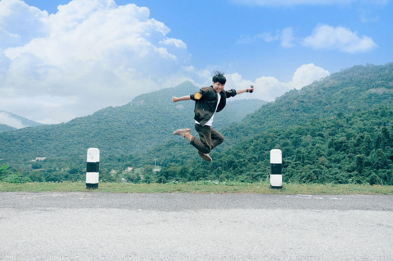 Rear view of man jumping on road against sky