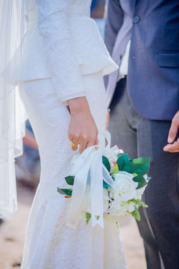 Midsection of bride holding bouquet while standing with groom during wedding ceremony