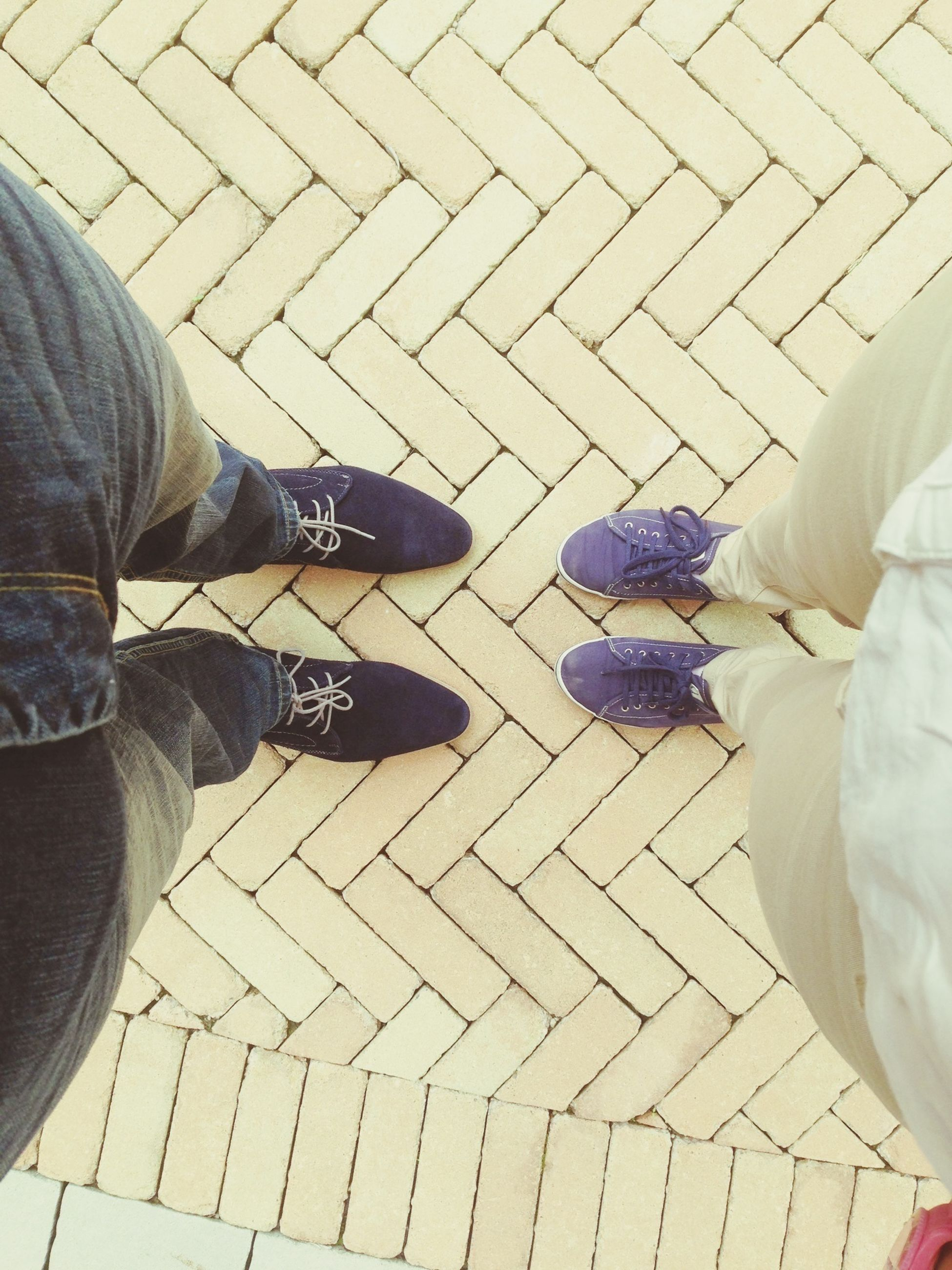 low section, person, lifestyles, high angle view, men, shoe, leisure activity, standing, personal perspective, human foot, cobblestone, casual clothing, paving stone, footwear, tiled floor