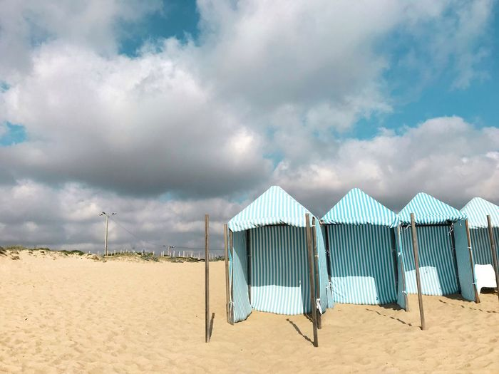 Huts At Beach Against Cloudy Sky