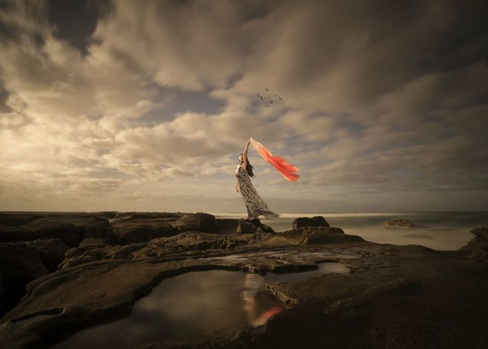 Woman Holding Scarf Standing On Rocky Shore Against Cloudy Sky During Windy Weather