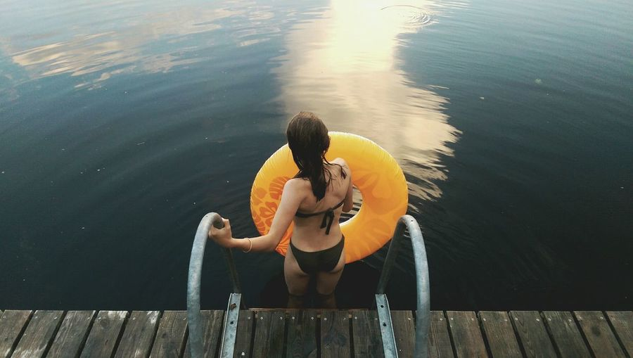 Rear View Of Woman With Inflatable Ring While Standing In Lake