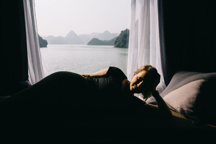 Boat Cruise Through Halong Bay, Vietnam Adults Only Bay Boat Carefree Cruise Curtain Curtains Halong Bay Vietnam Holiday Holidays Living Room Ocean One Person People Relaxation Relaxing Moments Southeast Asia Travel Travel Destinations Vacation Vacation Time Vietnam Water Window Window View