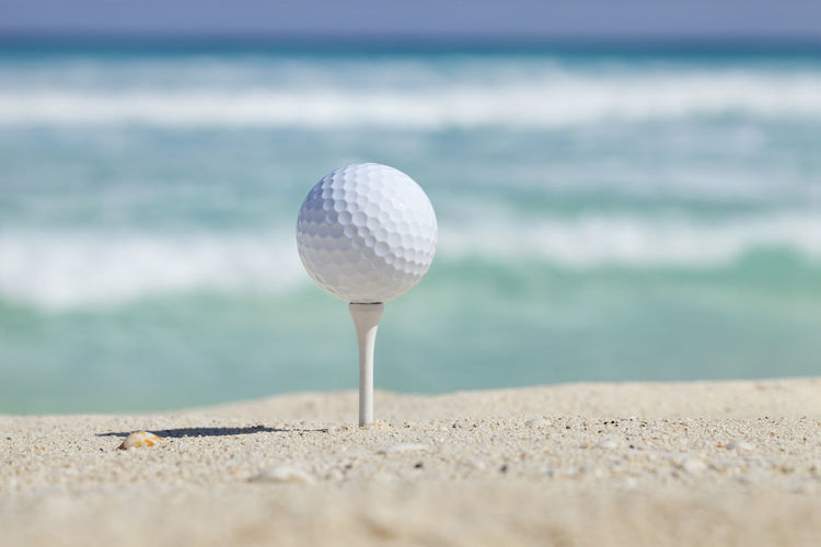 Golf ball sits on tee on sandy beach with surf in background Beach Close-up Day Focus On Foreground Metal Nature No People Outdoors Pattern Protection Sand Sea Selective Focus Shore Single Object Sphere Still Life Sunlight Surface Level Tranquility Genuine Brazil Images