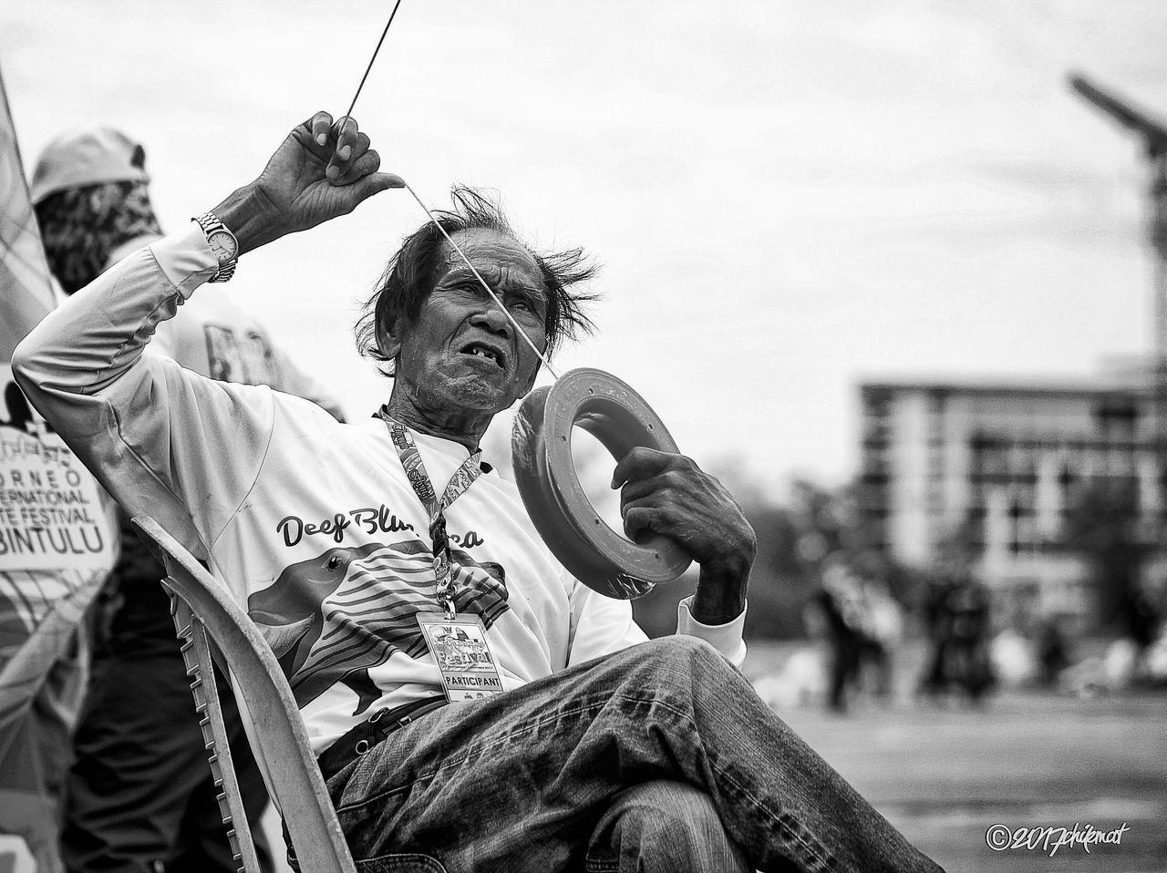 MAN SITTING ON HOLDING UMBRELLA