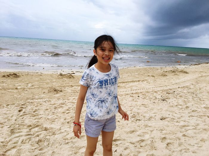 Portrait of happy girl standing on beach against sky
