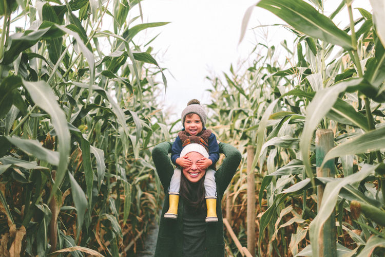 Mother Agriculture Cheerful Crop  Day Fall Field Fun Happiness Landscape Lifestyles Looking At Camera Men Outdoors Plant Portrait Real People Shoulders Smiling Son Standing Toddler  Togetherness Two People Women Human Connection