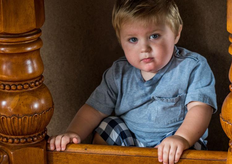 Portrait of cute baby boy sitting under table