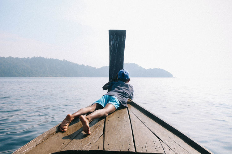 Beauty In Nature Day Full Length Leisure Activity Lifestyles Nature One Person Outdoors Pier Real People Relaxation Scenics - Nature Sea Sitting Sky Tranquility Water Wood - Material