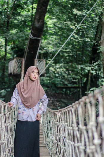 Woman wearing hijab standing on rope bridge against trees in forest