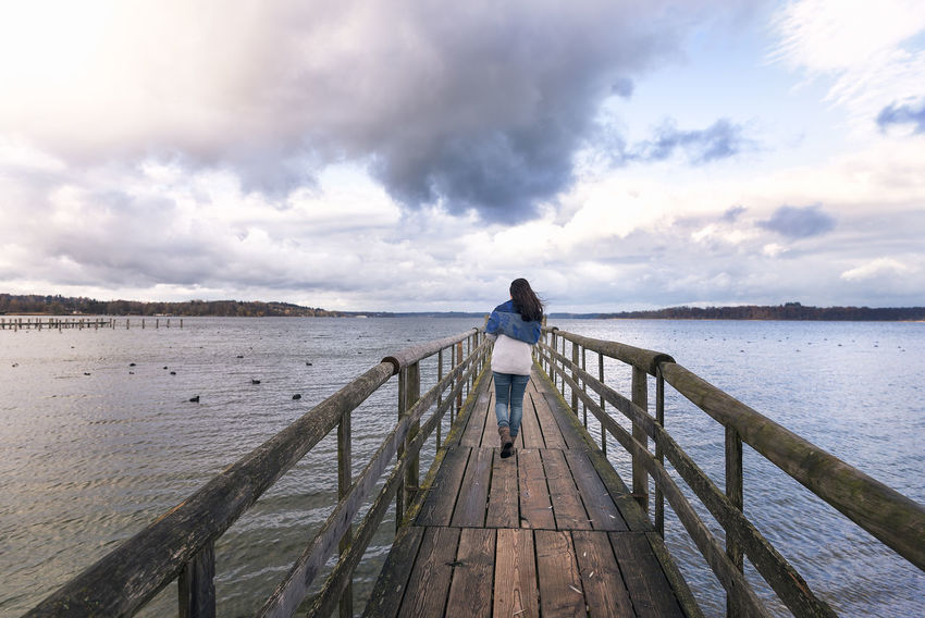 Young woman walking alone on a rustic wooden bridge over the Chiemsee lake, also called the Bavarian Sea, located near Rosenheim, Germany. Bavaria Bavarian Lakes Beauty In Nature Chiemsee Cloud - Sky Early Winter Germany Horizon Over Water Leisure Activity Nature One Person Railing Scenics Sky Tranquil Scene Tranquility Water Women Young Woman Young Woman Walking