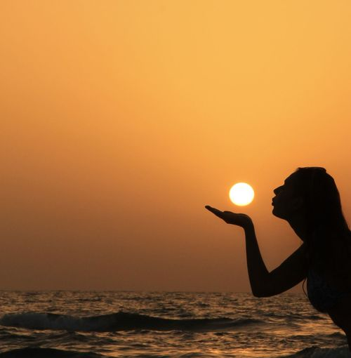 Optical illusion of silhouette woman holding sun against sea during sunset