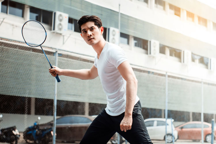 badminton player in sport outfit posing for a shuttle with a racket.Playing badminton at outdoor.Healthy lifestyle concept. Adult Architecture Ball Court Holding Leisure Activity Lifestyles Motion One Person Outdoors Playing Racket Sport Sports Clothing Tennis Tennis Racket Three Quarter Length Young Adult Young Men