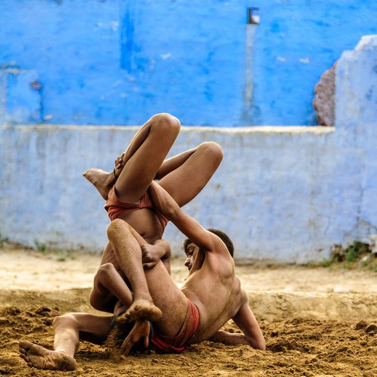 Two young athletes practice the traditional Indian version of wrestling, just a few hundred meters from the world famous Taj Mahal in Agra, Uttar Pradesh, India. Athlete India Indian Indian Culture  Barefoot Lifestyles Match - Sport Men Real People Sand Shirtless Skill  Traditional Training Upside Down Wrestler Wrestling Young Adult