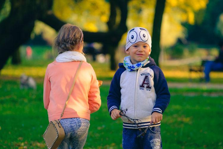 Siblings standing on field at park