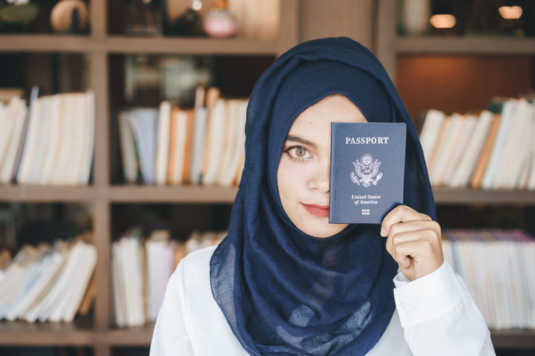 Portrait of young woman covering face with passport