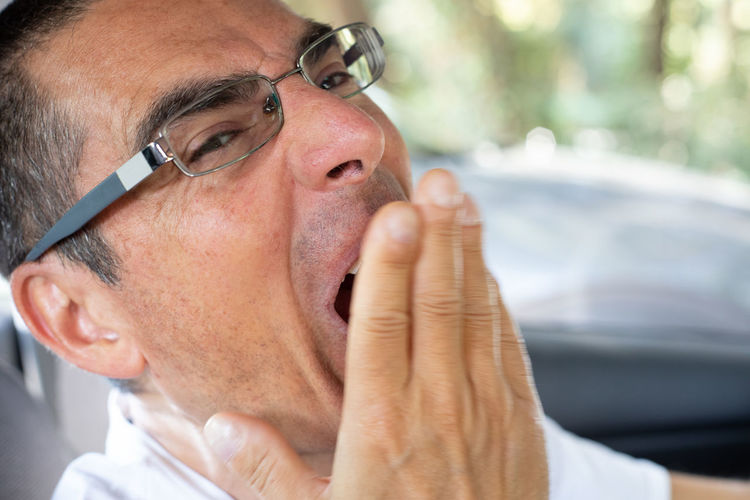 Close-up portrait of man yawning in car