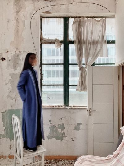 Young woman standing on chair while looking through window at abandoned home