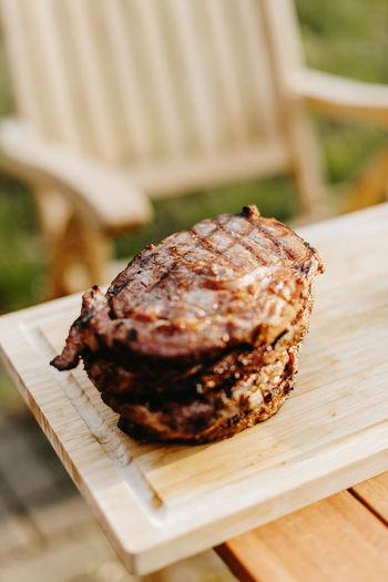 Well done dry-aged rib eye steak on a cutting board outside in the summer sun