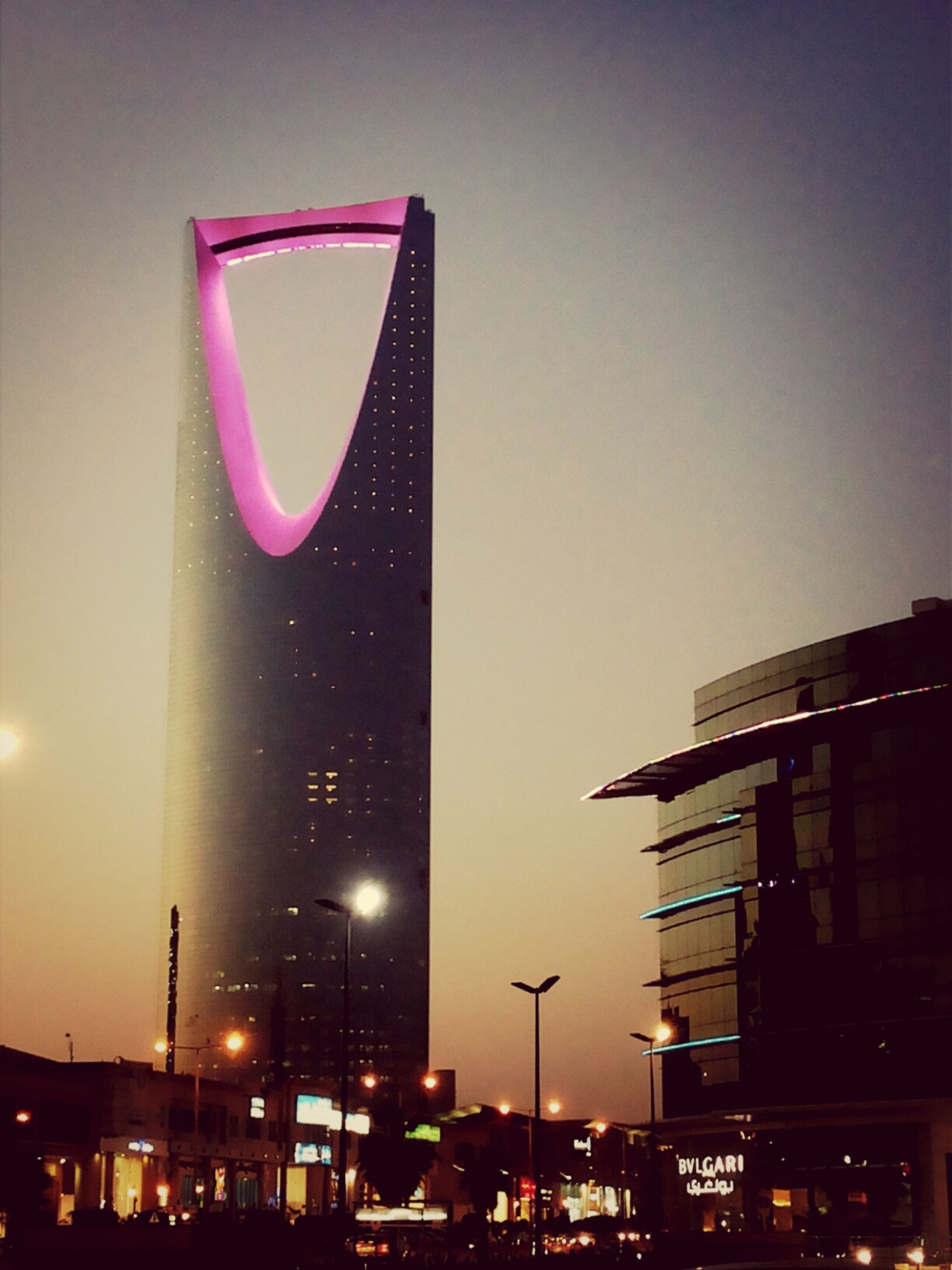 building exterior, architecture, built structure, low angle view, city, illuminated, building, clear sky, sky, night, street light, city life, dusk, road signal, modern, outdoors, skyscraper, communication, lighting equipment, office building