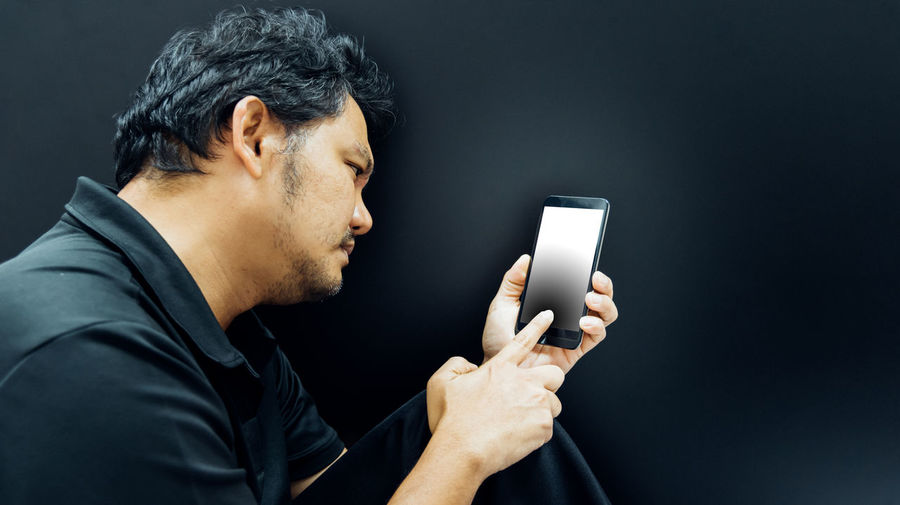Midsection of man using mobile phone against black background