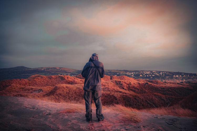 Full length of man standing on street against sky during sunset
