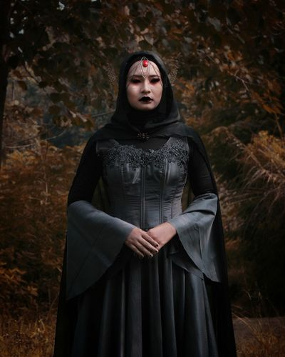 Portrait of young woman in halloween costume standing at forest during autumn