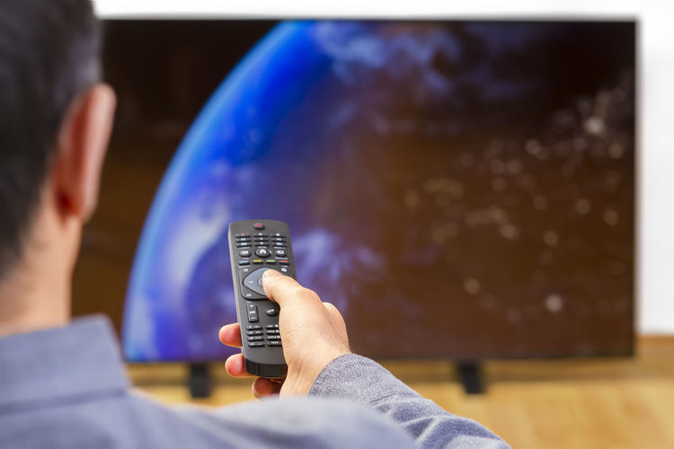 Rear view of man holding remote control while watching television
