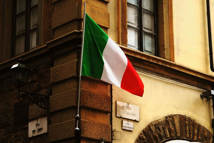 Low Angle View Of Italian Flag Against Building