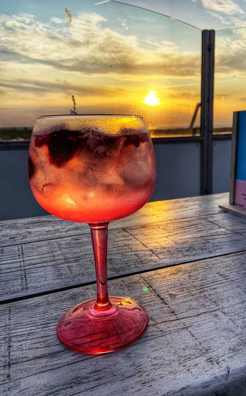sunset, sky, table, close-up, food and drink, drink, orange color, no people, cloud - sky, refreshment, glass, freshness, glass - material, still life, alcohol, focus on foreground, transparent, nature, food, outdoors, cocktail, aperitif