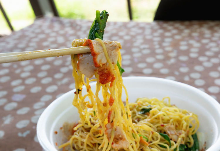 Close-up of noodles in bowl on tablecloth