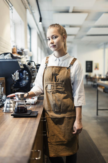 Young woman standing by coffee at cafe