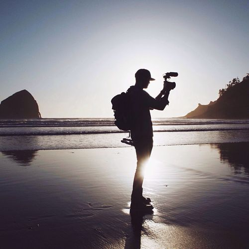 Side View Of Silhouette Man Video Recording On Beach During Sunset
