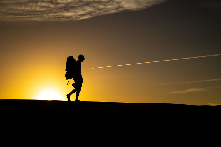 Silhouette man walking against sky during sunset