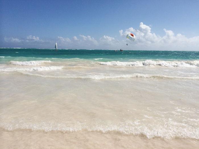Parachute over sea against sky