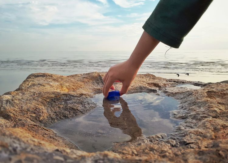 Cropped hand of girl holding bottle cap in sea against sky