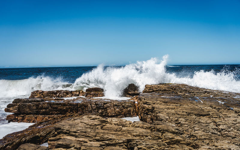 Waves splashing on rocks against clear sky