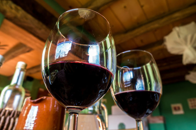 Glass of red wine on a table in rustic restaurant Drink Wine Alcohol Wineglass Refreshment Food And Drink Glass Red Wine Indoors  Focus On Foreground Glass - Material Close-up Still Life No People Table Freshness Transparent Bottle Drinking Glass Food Winetasting