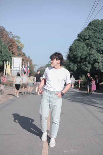 Full length of young man walking on road in city