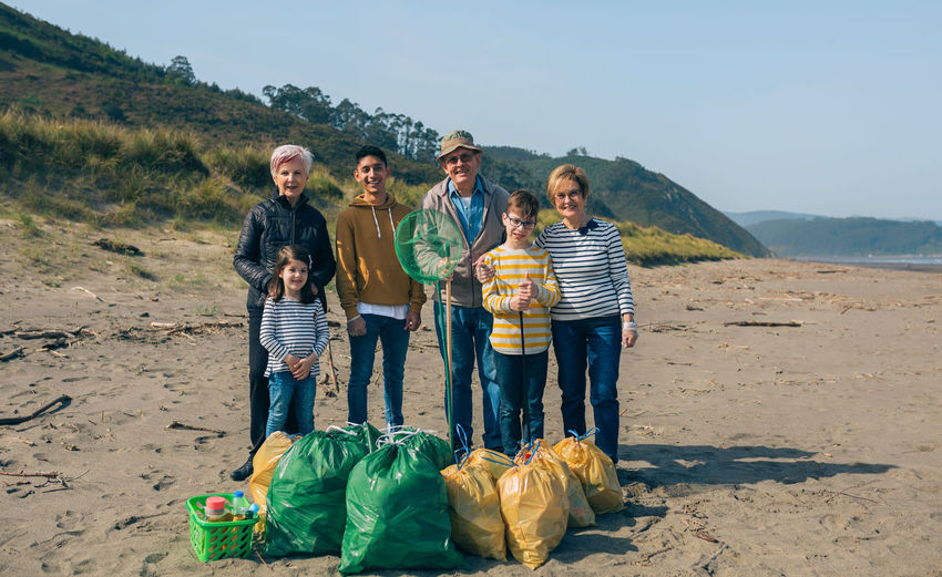 Portrait of happy family standing after cleaning at beach