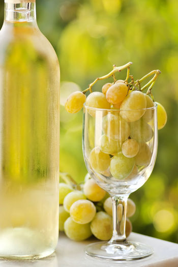 Close-Up Of Wine Bottle By Grapes Filled Wineglass On Table