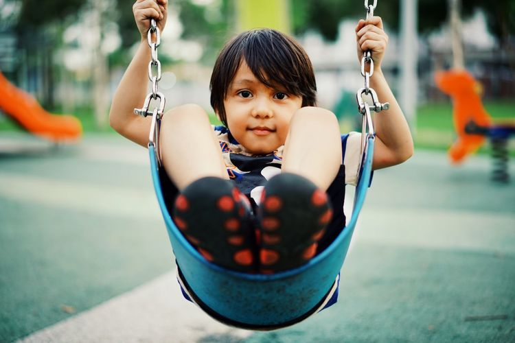 Portrait of boy sitting on swing at playground