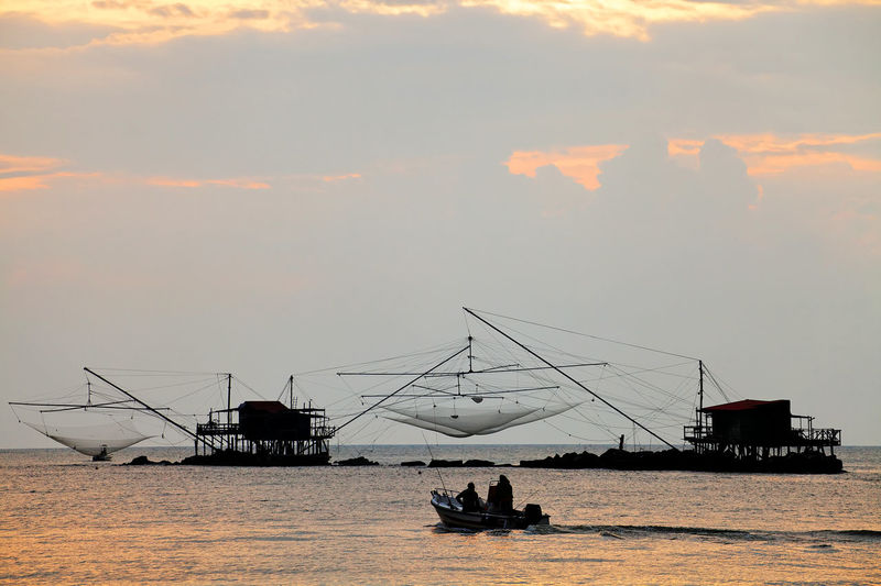 Fishing nets on sea during sunset
