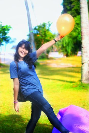 Smiling young woman with balloons at park