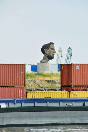 Poseidon is greeting No People Statue Lüpertz Harbour Cruise Ruhrort Red Blue Cranes Cargo Container Industry Bird Commercial Dock Business Finance And Industry Harbor Business Freight Transportation Sky